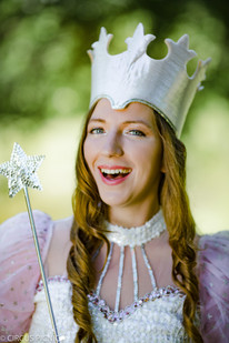 Glinda the good witch is smiling with her magic wand at a CIRCUS PICNIC Wizard of Oz themed party.