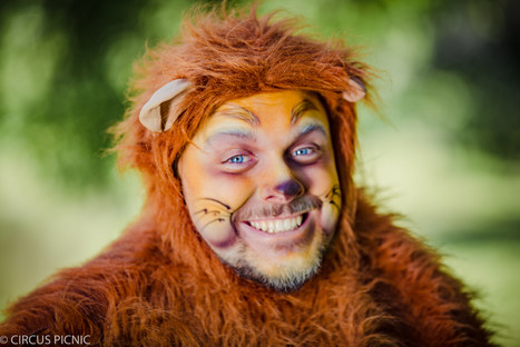 The cowardly lion is smiling for a picture at the Wizard of Oz themed party
