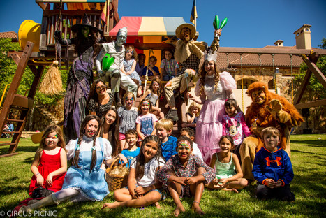 Kids are on a playground posing for a picture with the Wizard of Oz characters