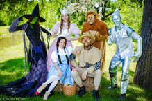 The Wizard of Oz characters are posing for a photo at the CIRCUS PICNIC party.