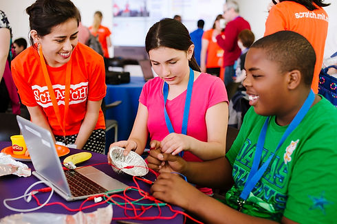 Two students and a volunteer creating a project with makey makey at scratch day