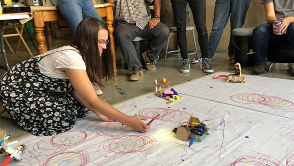 Workshop participant trying out her light-powered scribble bot