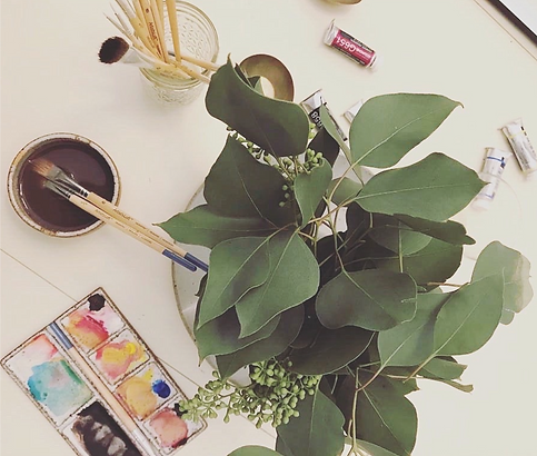 Messy but artful desk with eucalyptus leaves in a vase and paints.