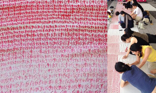 """Protestors write 500,000 times the words """"Against"""" to represent the number of ignored dissenting signatures received in the public consultation stage. Photo by Hin-yan Wong / Hofan Chau"""