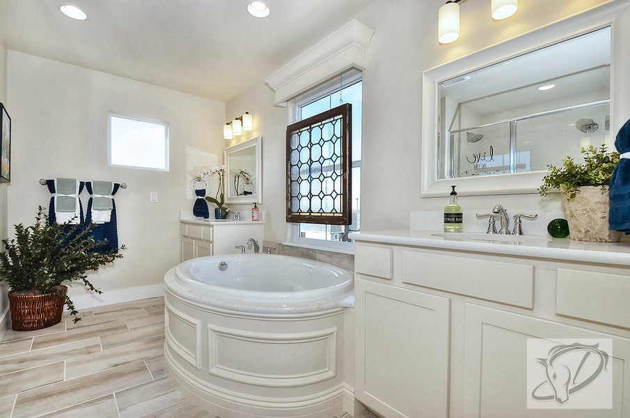 Master bathroom with custom wood paneled bathtub and stained glass