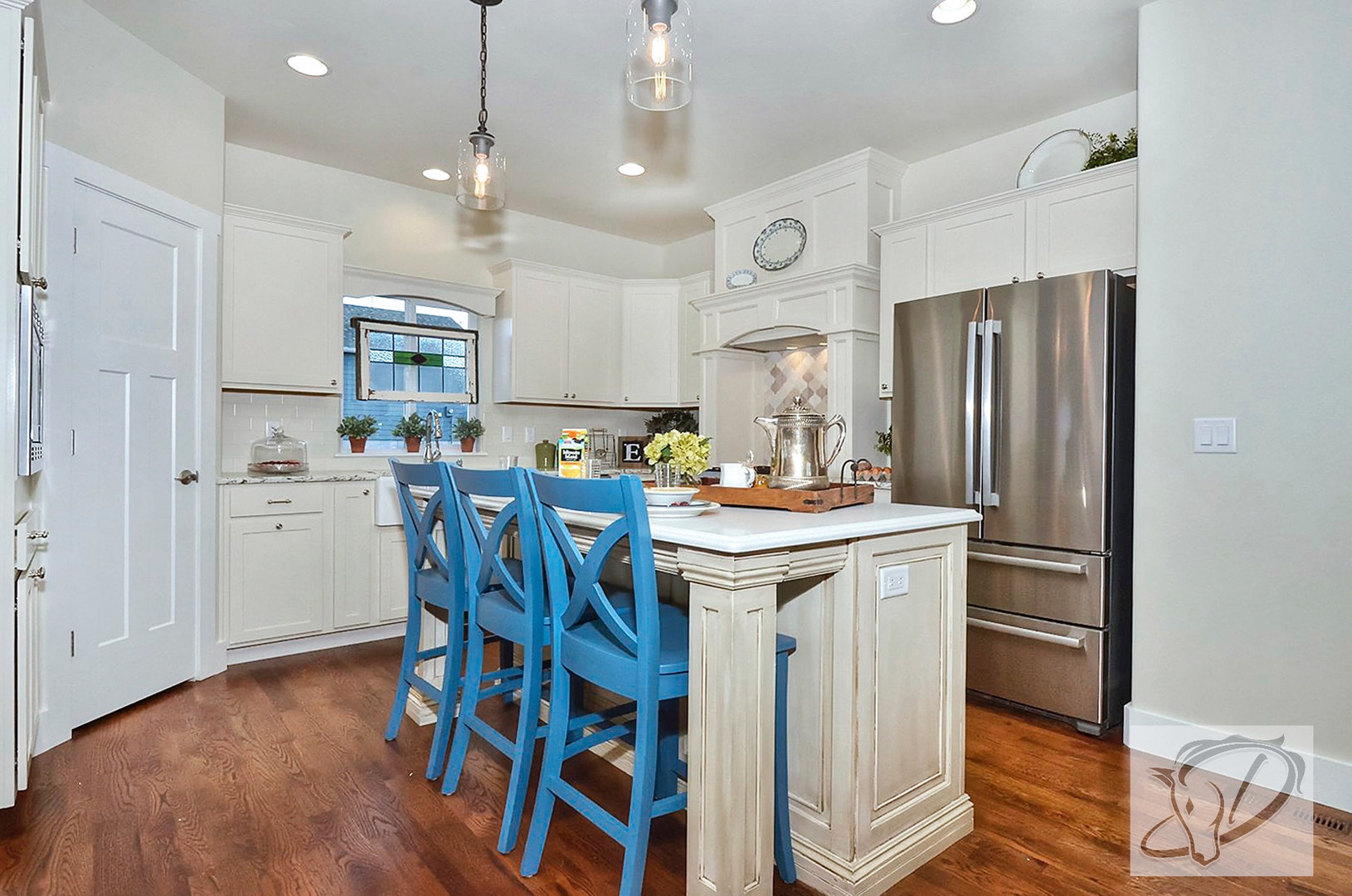 Charming craftsman kitchen with custom range hood, antique white cabinets, farmhouse sink, stained glass and buffet (purchase out of a storage unit) re-purposed into a custom island