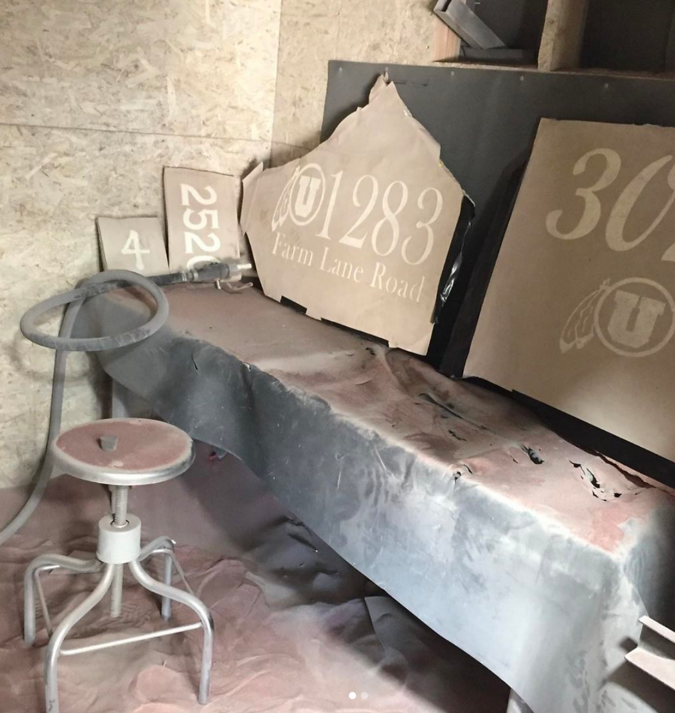 sandblasting booth with multiple slabs of stone propped up on a table. Stones are masked with paper and show addresses that have been blasted into the stones' surfaces.