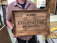 A wooden tray is held by a man in a plaid shirt. The tray has been laser etched on the inside bottom to read Celebrating 15 Years with the awarding company name also laser etched above the main text.