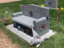 A memorial bench in a cemetery. Granite bench features the surname Holler in a banner with a portrait of a man and woman etched below. Other flourishes and text are on the side of the bench and front of the seat.