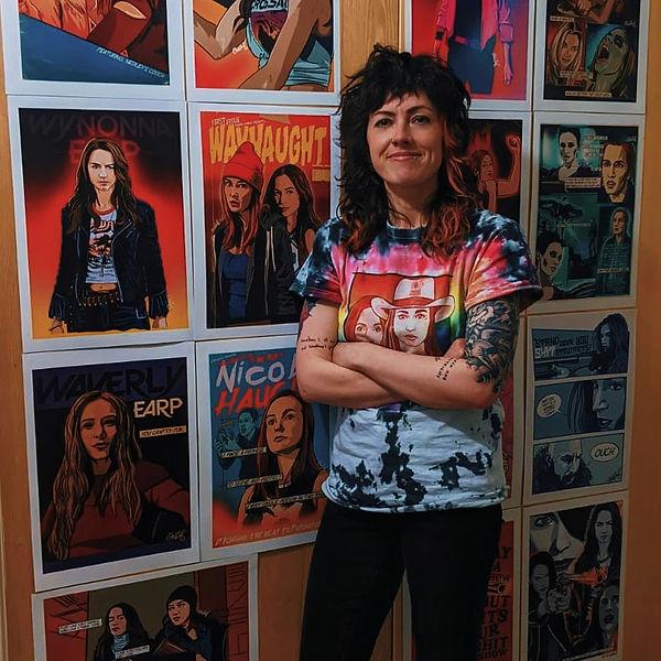 Artist Hayley Bosworth standing in front of her Wynonna Earp artwork.