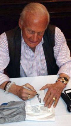 Buzz Aldrin signing a primary earth and space workshop glove