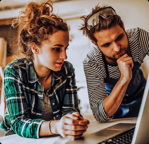 Mladý pár řeší na počítači design webu