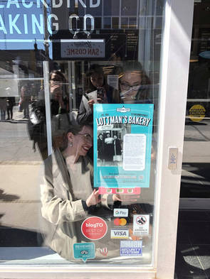Casarina and Evelyn installing one of the Lottman's posters in the window of Blackbird Baking Co., 172 Baldwin St. Photo Credit: Erica Chi.