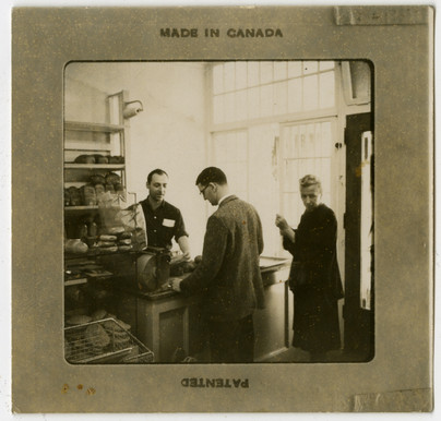 "Morris ""Moishe"" Perlmutar serving customers in A. Perlumtar Bakery, ca. 1950s. OJA, accession 2019-1-5."