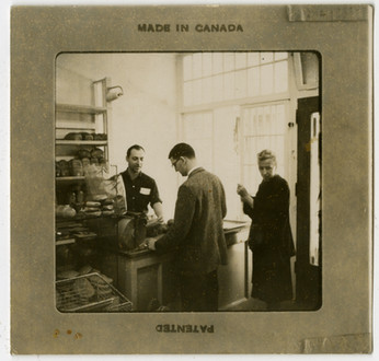 """Morris """"Moishe"""" Perlmutar serving customers in A. Perlumtar Bakery, ca. 1950s. OJA, accession 2019-1-5."""
