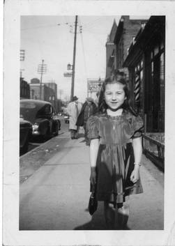 Dworkin's sign appears in the background of this photograph of a young girl, ca. 1945. OJA, item 4015.
