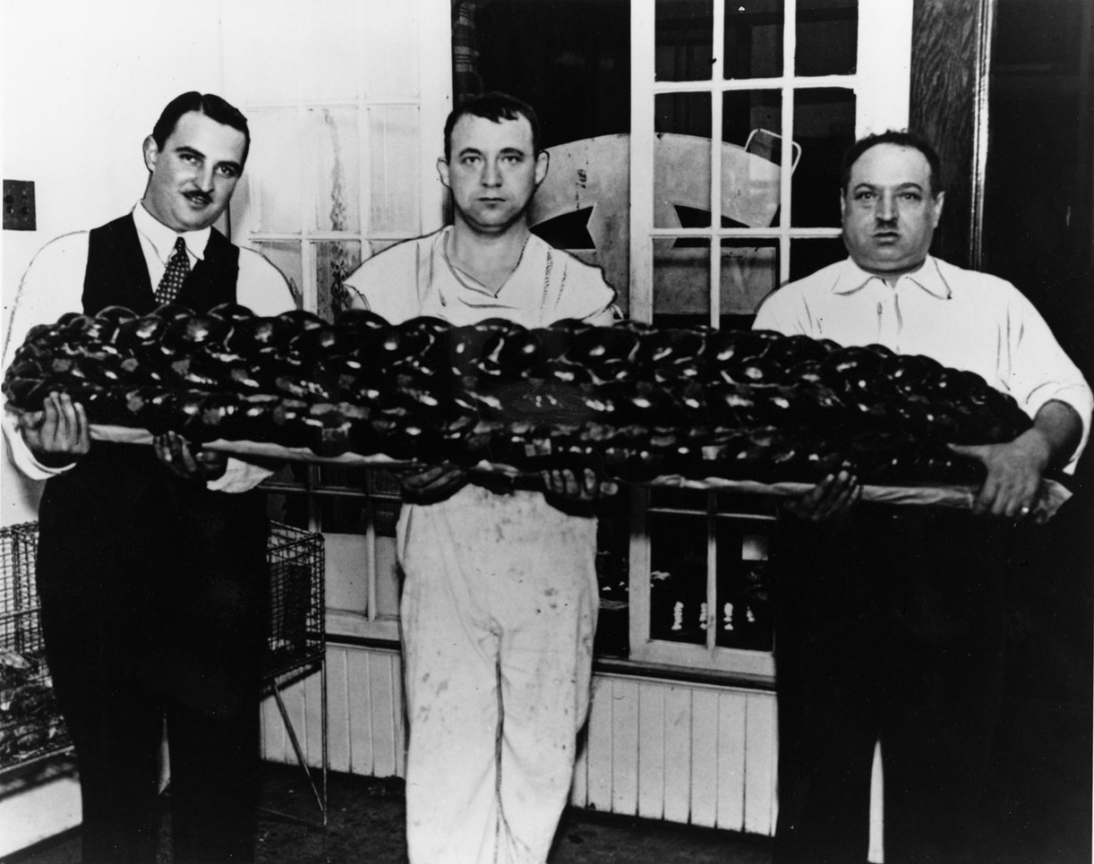 Ben Zalvin, Harry Elishevitz, and Arrin Perlmutar (left to right) holding a 99lb challah, 1938. OJA, item 4495.