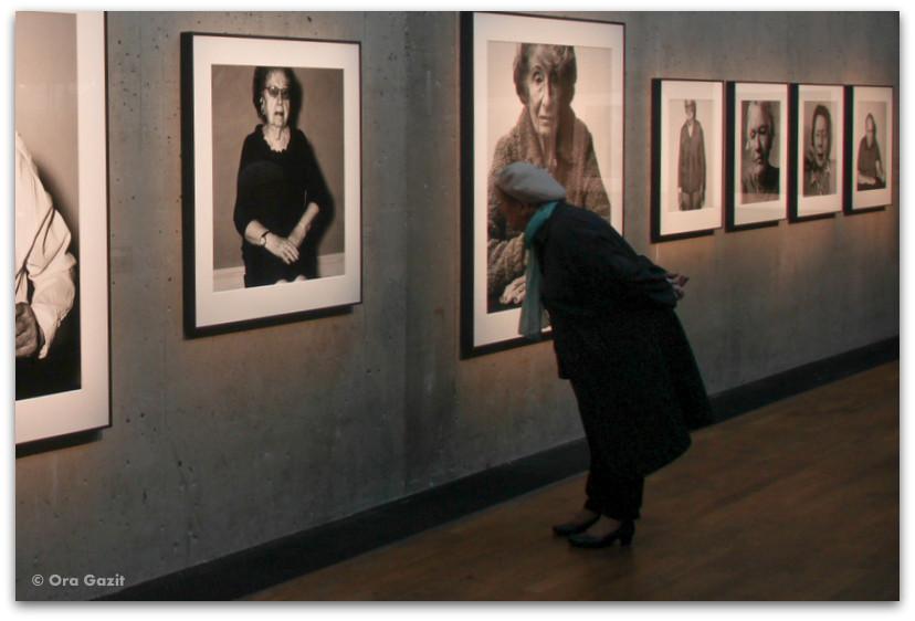 אשה מתבוננת בתמונות - תערוכת צילום - שטוקהולם