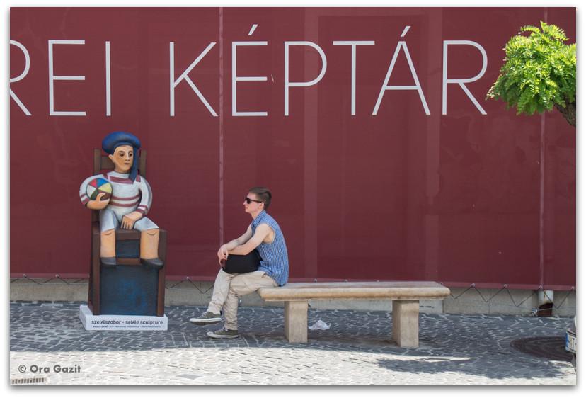 איש יושב ליד פסל - סנטאנדרה