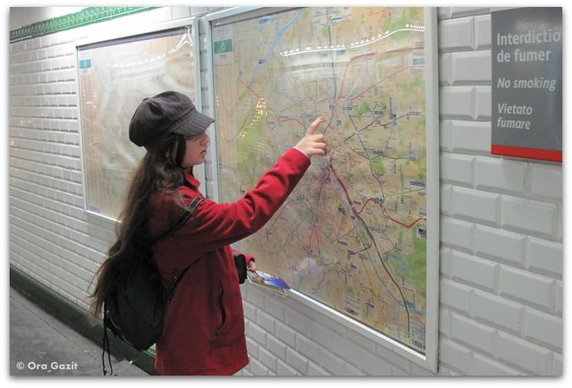 ילדה מסתכלת במפה. מטרו. פריז