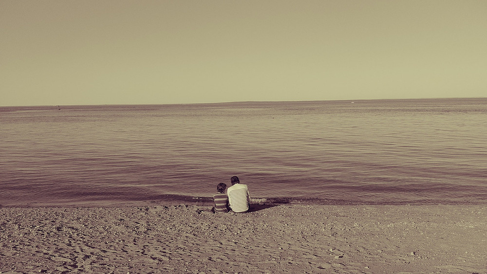 father and son sitting on empty beach looking out on water