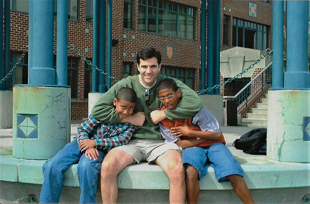 Adult mentor hugging young mentees