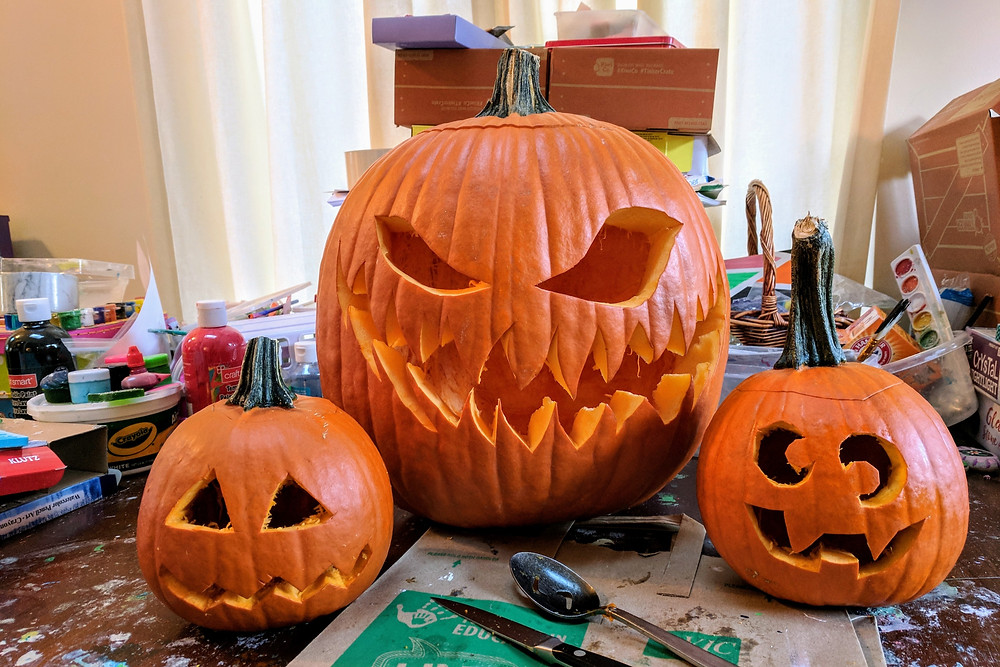 Three carved jack-o-lanterns on cluttered art table