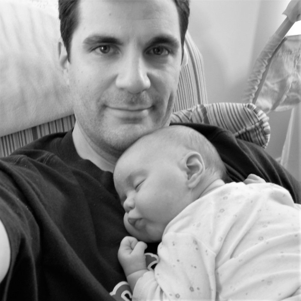 Dadvocacy Consulting Group Director of Communications Scott Beller with infant daughter asleep on chest