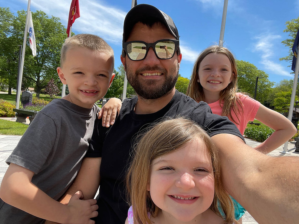 Smiling dad with son and two daughters