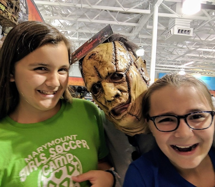 A masked DCG Communications Director Scott Beller Halloween costume shopping with daughters