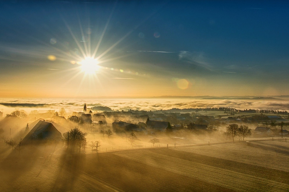 Landscape, town, and fog at sunrise
