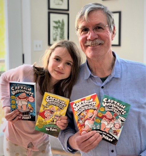 Rob Richardson with granddaughter holding Captain Underpants books