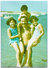 Dadvocacy Consulting Group founder Allan Shedlin carrying three young daughters at beach