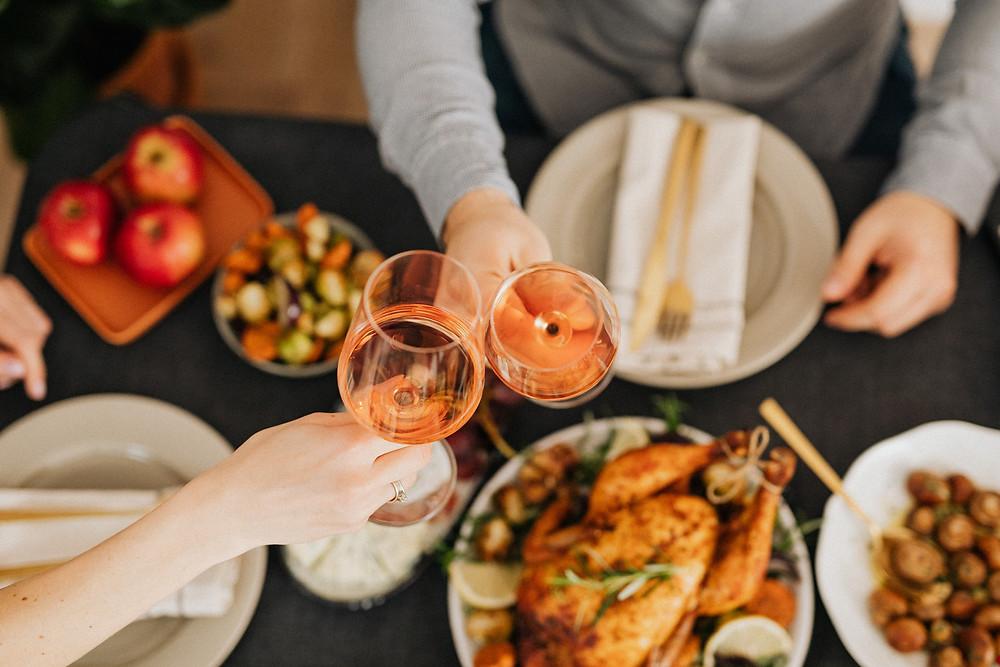 People seated at table toasting with champagne during Thanksgiving dinner