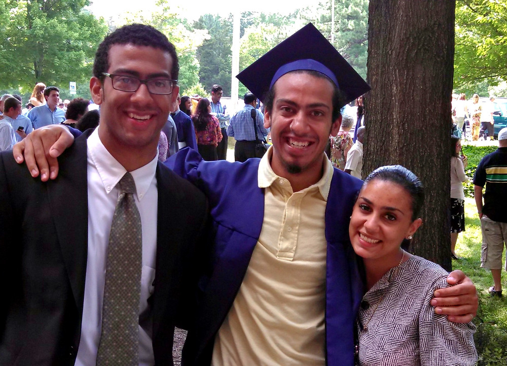 High school graduate posing with his brother and sister