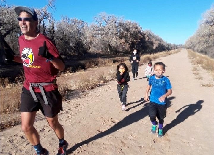 Anthony running race with his kids, wife trailing him to support