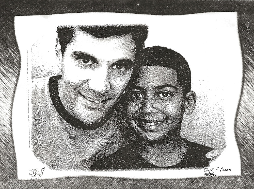 Adult male mentor and young boy mentee at Chuck E. Cheese restaurant