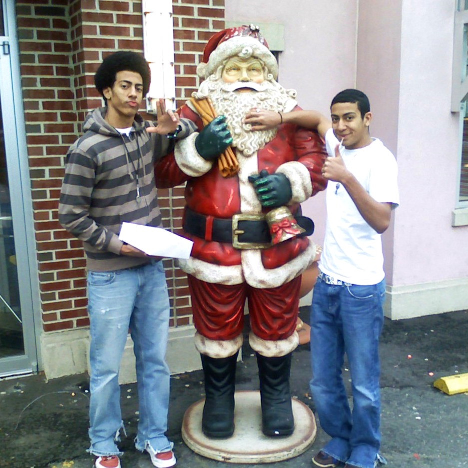 two brothers pose in front of Santa Claus statue