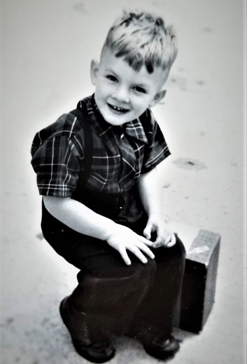 Young boy sitting on suitcase