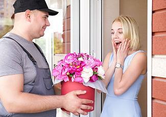 Young woman receiving beautiful peony fl