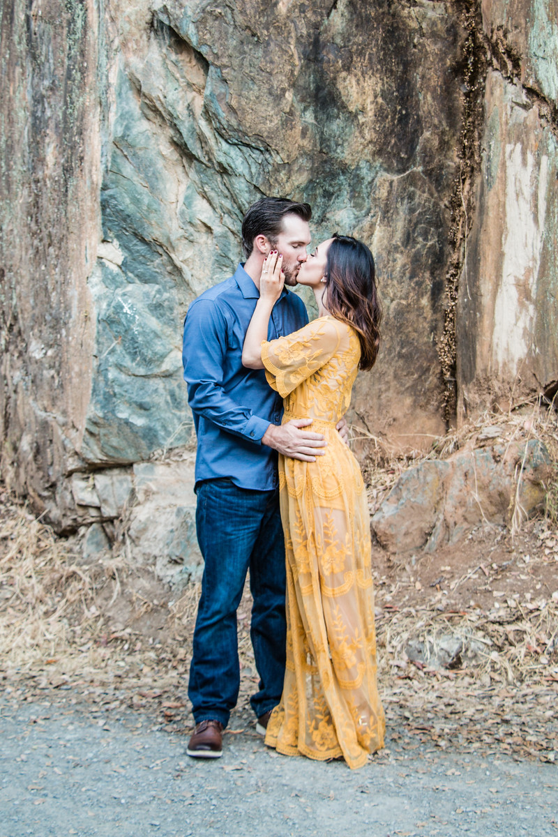 Auburn California, gorgeous couple kissing during engagement session in front of large rock wall