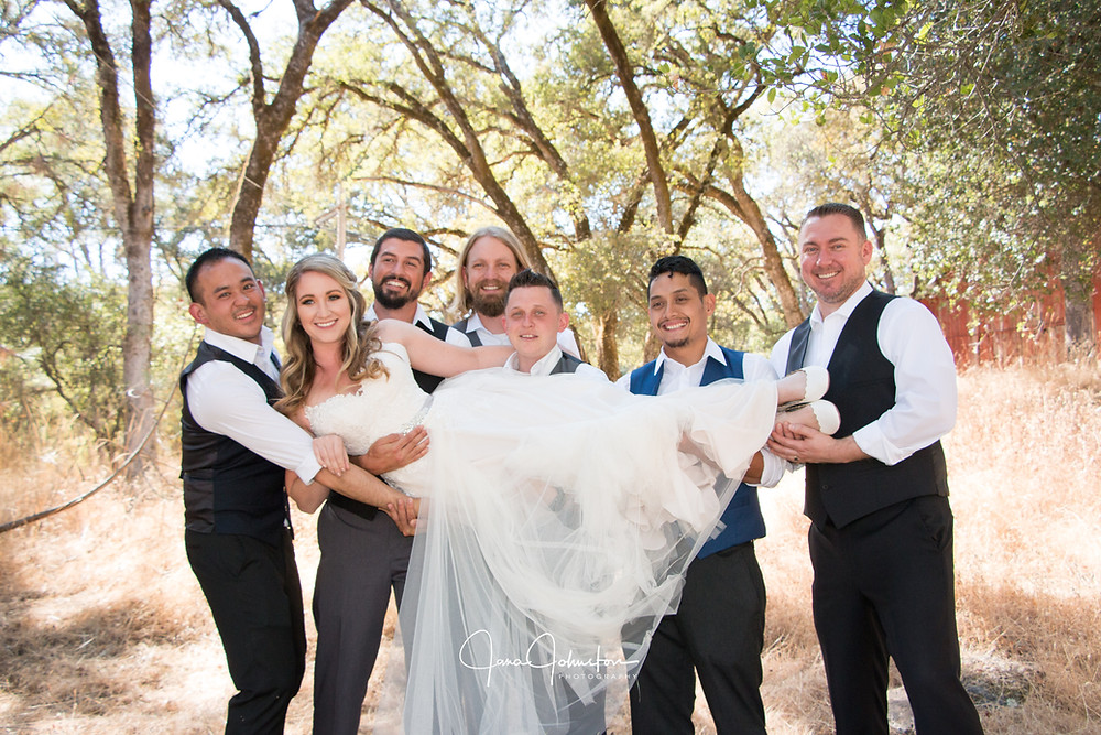Bride being held by 6 groomsmen