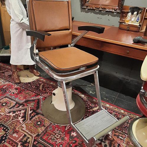 Oude bruine kappersstoel