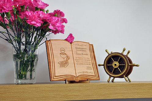 Pamiątka Pierwszej Komunii Świętej w kształcie otwartej książki.