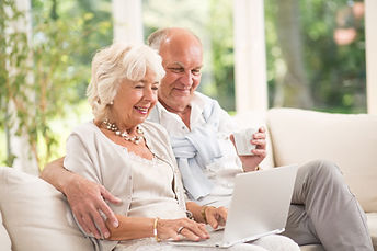 Elderly couple looking at a laptop together