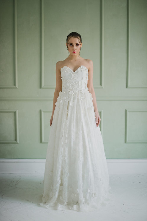 A wedding dress designed by a handmade designer in ivory and lace decorated with flowers
