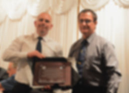 Chief Instructor Kris Richardson receiving his plague from Master Graham Moulden