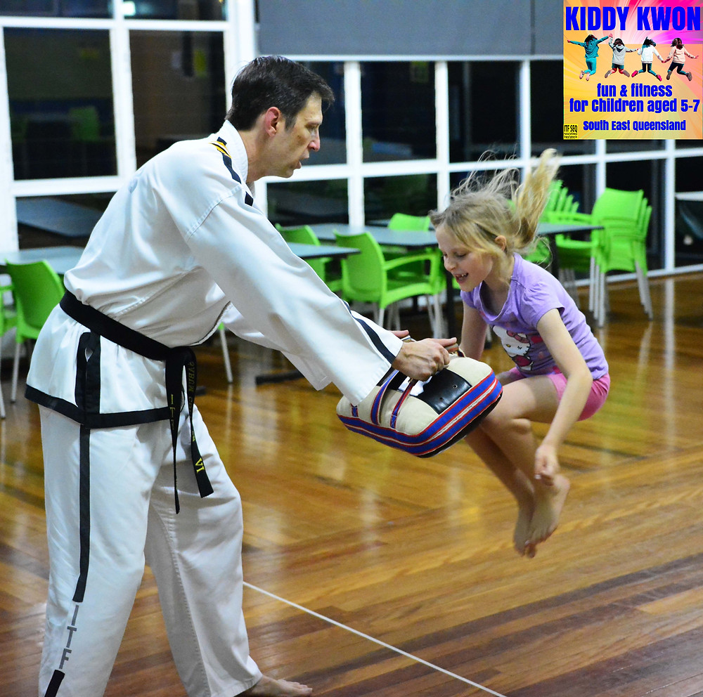 Young girl learning to jump with Taekwon-Do instructor