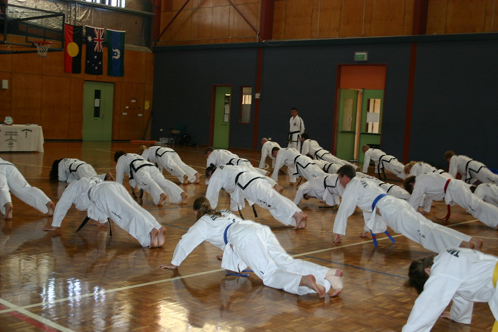 Taekwon-Do students doing puchups as part of a big class with only one instructor