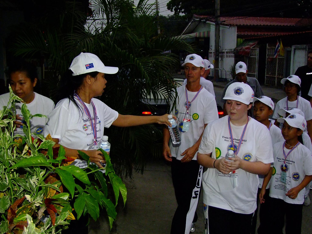 Sabum Rachanok handing out water to Sabum Jeff and AI Leah after their 5am run through the streets of Singburi, Thailand